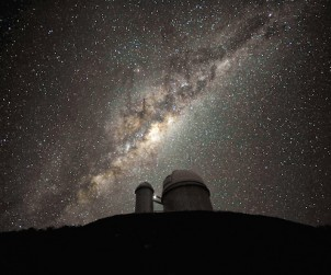 "The ESO 3.6-metre telescope at La Silla, during observations. The Milky Way, our own galaxy, stretches across the picture: it is a disc-shaped  structure seen perfectly edge-on. Above the telescope´s dome, here  lit by the Moon, and partially hidden behind dark dust clouds, is  the yellowish and prominent central bulge of the Milky Way. The whole  plane of the galaxy is populated by about a hundred thousand million stars, as  well as significant amounts of interstellar gas and dusts. The dust  absorbs visible light and reemits it at longer wavelength, appearing  totally opaque at our eyes. The ancient Andean civilizations saw in  these dark lanes their animal-shaped constellations. By following the  dark lane which seems to grow from the centre of the Galaxy toward the  top, we find the reddish nebula around Antares (Alpha Scorpii). The  Galactic Centre itself lies in the constellation of Sagittarius and  reaches its maximum visibility during the austral winter season. The ESO  3.6-metre telescope, inaugurated in 1976, currently operates with the  HARPS spectrograph, the most precise exoplanet ""hunter"" in the world.  Located 600 km north of Santiago, at 2400 metres altitude in the outskirts of  the Chilean Atacama Desert, La Silla was first ESO site in Chile and  the largest observatory of its time. This photograph was taken by ESO Photo Ambassador Serge Brunier. Links  ESO Photo Ambassadors webpage."